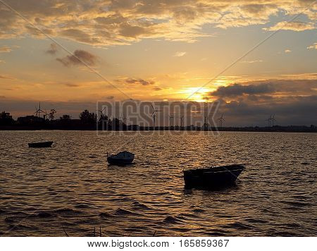 The boats from the Gulf of Puck. Puck, Poland - June 16, 2014 The equipment floating on the water of the Gulf of Puck in the rays of the setting sun.