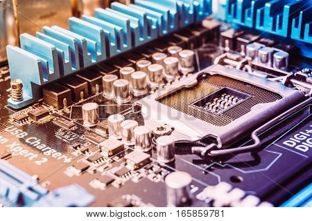 Printed circuit board with microchips and other electronic components. Socket for pc processor on mother board. Toned image.