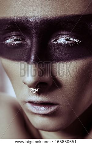 Beauty fashion shot of young man with nose rings and black strip line makeup and white eyelash. Male beauty portrait. studio shot.
