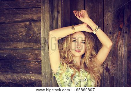 Portrait of a Beauty Hipster Girl on Wooden Background. Fashion Woman Outdoors with Hands over Head. Stylish Teenage Female. Toned Photo with Copy Space.