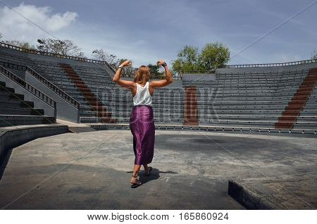 strong young woman enters a stadium with the will to win