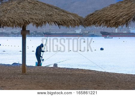 Man Fishing At The Red Sea, On The Beach Of Eilat, Israel