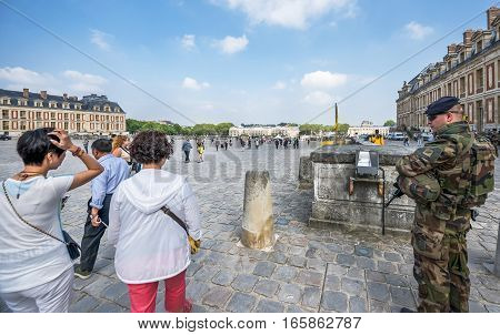 Versailles, France - June 2016: Tourists and military patrol in the yard of the palace
