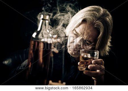 Studio shot with black background of senior man drinking hard