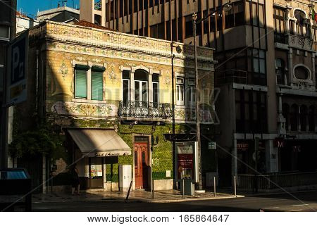 Old building in bright afternoon light lisbon, portugal july2015 framed by shadows and strong contrast