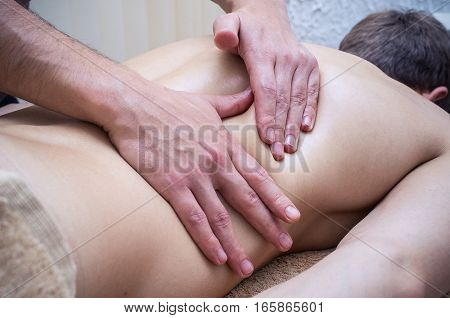 Man's hands making massage of the back