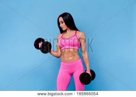 Muscular woman in pink leggings, top and gloves holding dumbbells. Isolated