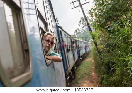 Blonde caucasian woman looking trough old retro blue train window , traveling by train in third world country.
