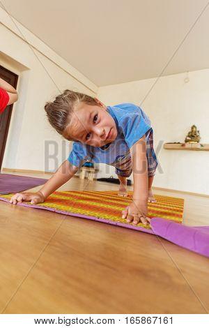 Little boy on a yoga class with a beautiful yoga mat