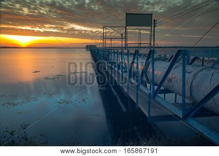 Water pipe and water sucker station in the dam during sunrise