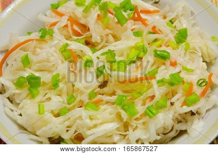 Pickled chopped cabbage with carrots and green onions.