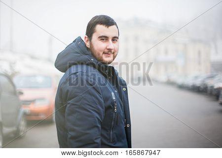 Happy bearded man walking through foggy street