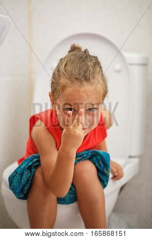 Boy in red shirt is sitting on the toilet
