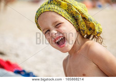 Beautiful baby resting on the beach near the sea