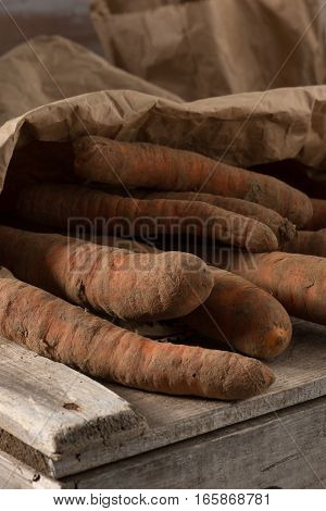 Closeup of organic carrots in a brown paper sack
