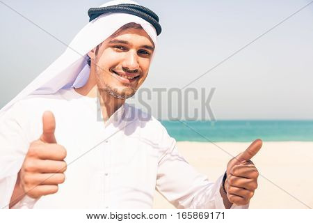 young arabian man standing on the beach, giving you a thumbs up