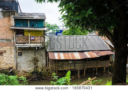 slums near dirty river with rooftop made from zinc photo taken in Depok Indonesia java