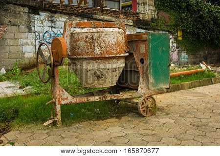 A dirty cement mixer abandoned in front of a house photo taken in Jakarta Indonesia java