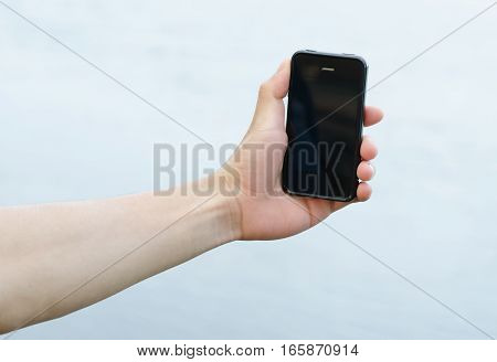 Closeup smartphone and hand on white background