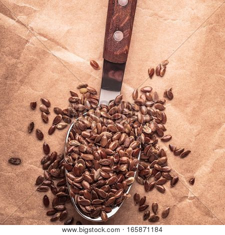 Healthy food. Flax seeds linseed on kitchen spoon old paper background. Square format