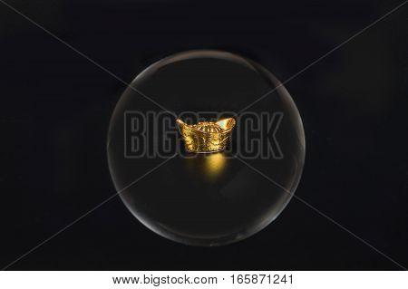 gold ingot money through glass crystal ball on black background