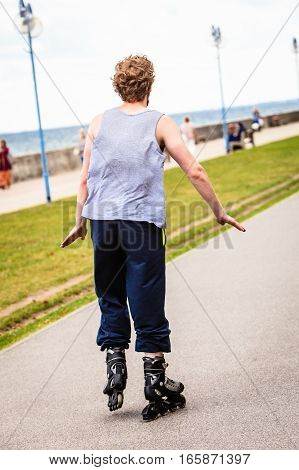 Outdoors activities sport and hobby.Wellbeing and exercising. Man have fun riding rollerblades in park spending free time in summer.