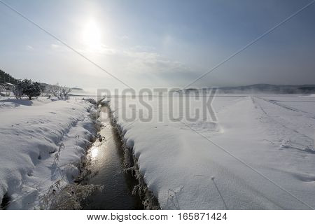 Snowy earth and agricultural waterway under blue sky with sun in Kagoshima