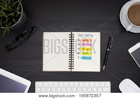 Smart goal setting on notebook with office supplies computer eye glasses and coffee cup over black table desk background view from above Business success concept