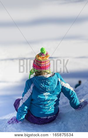Young Girl with back to camera sitting on snowy hill, ready to slide down.  She is dressed in colorful winter clothing.