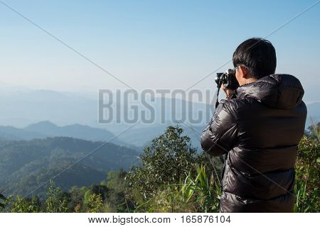 Young professional traveler man with camera shooting outdoor fantastic mountain landscape