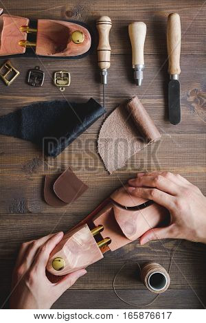 cobbler with tools work process dark background top view with hands