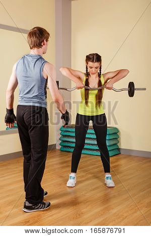 Coach man watching the girl to perform exercises with a barbell. Personal coach. Healthy lifestyle concept. Fitness.