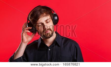 Man listening to your favorite music on headphones. He enjoys the melody. Hipster in a black shirt on a red background.