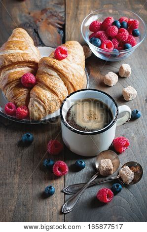 Coffee and croissants with raspberries and fruits for breakfast. Enamel mug. Toned image selective focus
