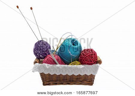 Knitting yarn balls and needles in basket isolated on white background