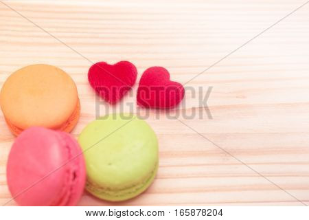Two red hearts with colorful macaroons on wood background vintage style