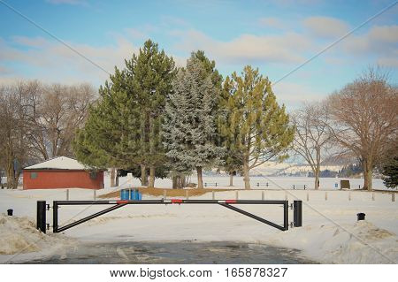 Winter landscape view of park entry gate in foreground. Red building, large trees on snow covered ground and lake in background. Bright blue sky and clouds.