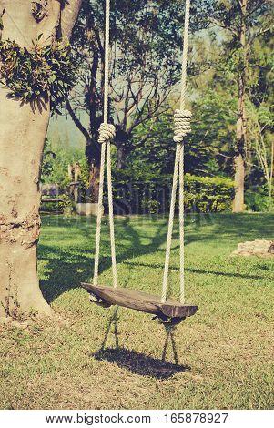 wooden swing in the garden vintage tone