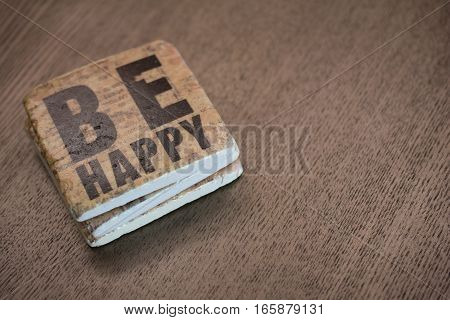 A set of stone coasters stacked on a wooden table surface reading Be Happy
