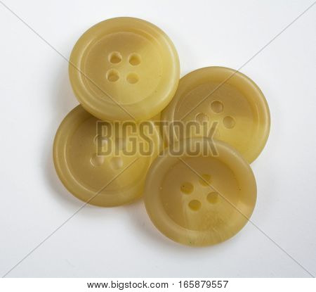 Four Cream Colored Plastic Buttons Stacked And Isolated On White