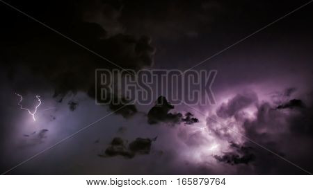 Lightning Bolt Discharges In Purple Storm Clouds At Night