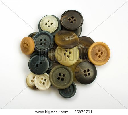 Pile Of Assorted Dark Buttons Isolated On White