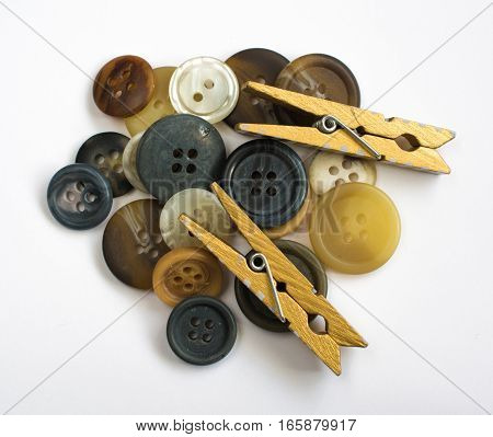Pile Of Assorted Colorful Buttons And Wooden Clothes Pins Isolated On White