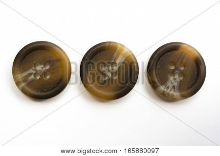 Three Brown Plastic Buttons Isolated On White