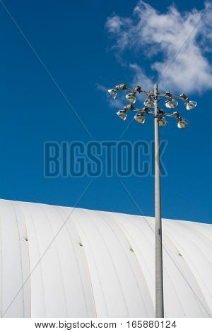 Stadium Dome With Lights On A Sunny Day