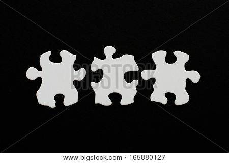 Three Blank Puzzle Pieces Inline Unlinked On Black Background