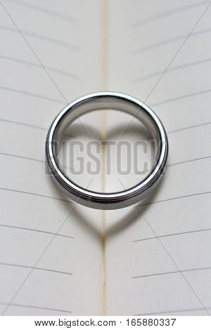 Wedding Ring Band On Book With Heart Shadow Close Up Top View