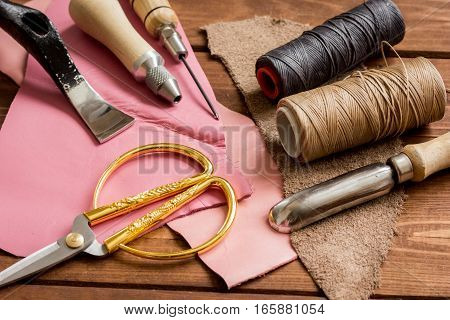 leather craft instruments on wooden background close up.