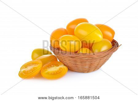 whole and half cut yellow cherry tomato in bamboo basket and on white background