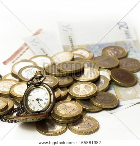 A square photo of a vintage style chain watch with a heap of euro money in coins and banknotes, on white background